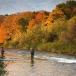 Two Men Fishing on Shore in Fall Foliage